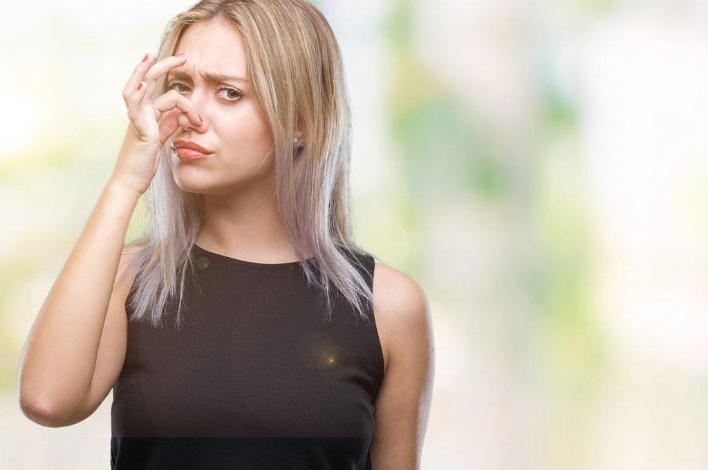 woman smelling something bad
