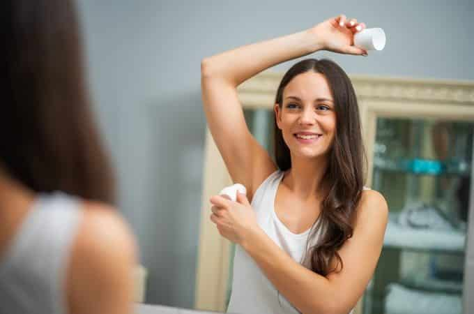 young girl applying underarm deodorant
